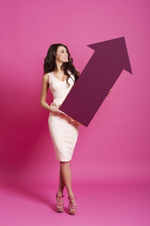 Attractive woman holding pink arrow sign   photo