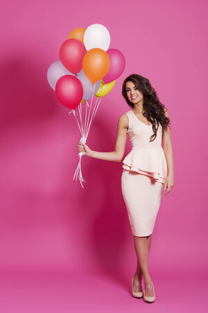 Beauty and fashionable woman with multi colored balloons photo