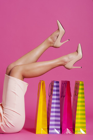 Low section of woman wearing high heels with shopping bags  photo