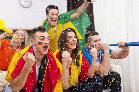 Grupo de personas multiétnicas celebra la victoria del equipo de fútbol favorito Foto de archivo
