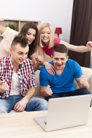 watching football: Excited friends watching soccer match on laptop  Stock Photo