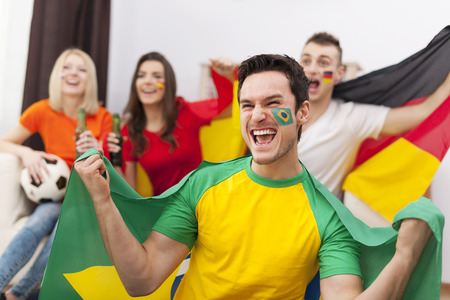 Excited brazilian man with her friends cheering football match photo