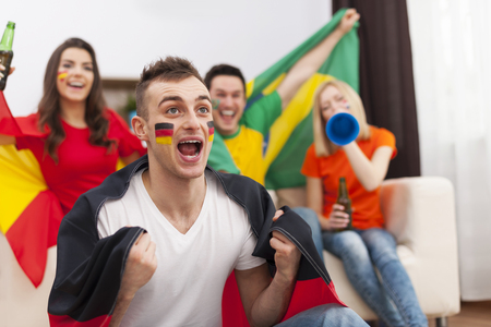 Excited german man with her friends cheering football match photo