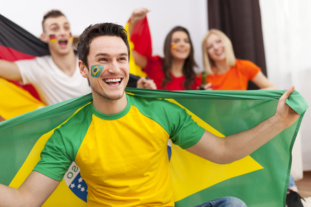 Brazilian man with friends from different country enjoying the soccer on TV photo