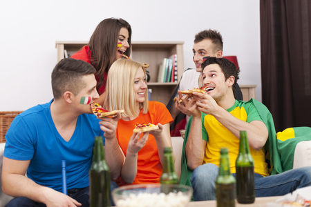 Group of multinational people eating pizza during the break in football match  photo