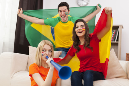 Group of multi national football fans cheering  Stock Photo
