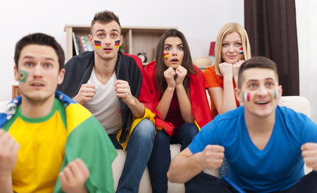 Portrait of young soccer fans during the watching match on TV  photo
