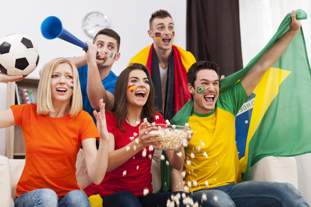 Group of multinational people cheering football match at home photo