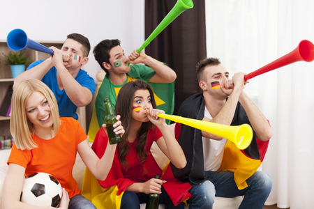 Multinational friends blowing by vuvuzela during the football match photo
