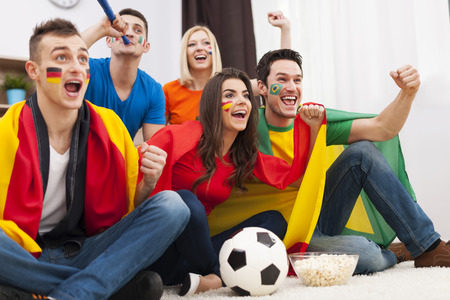 multinational: Group of multinational people cheering football match at home