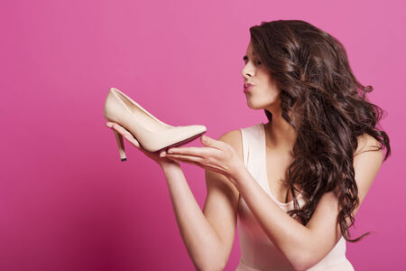 Beautiful female shopaholic kissing high heels  photo