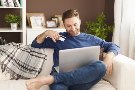 house shopping: Smiling man during online shopping at home