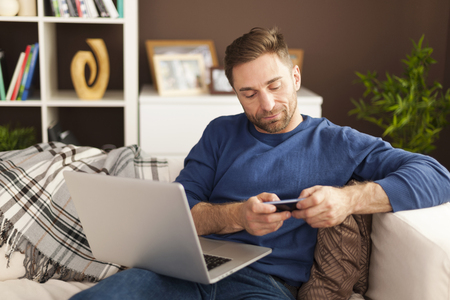 barefoot man: Focus man using mobile phone and laptop at home