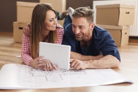Couple arranging new apartment with digital tablet   photo