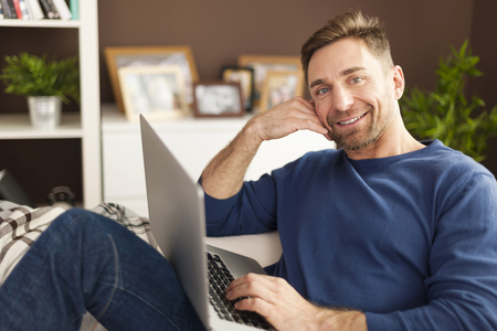 Portrait of smiling man with laptop on sofa  photo