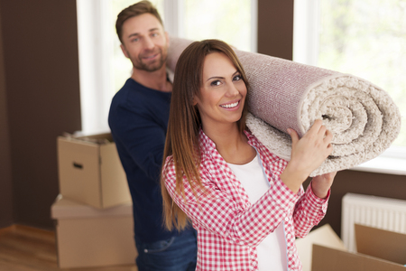 Portrait of happy couple carrying carpet for new home  photo