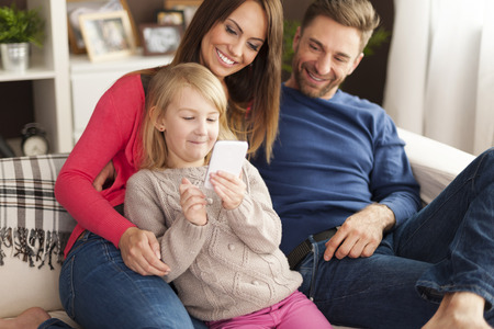 Cute little girl with parents playing by mobile phone at home  photo