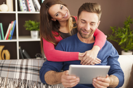 Embracing couple using digital tablet in living room  photo
