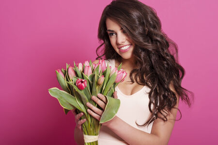 Natural smiling woman with bouquet of fresh tulips  photo