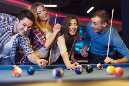 Groep jonge vrienden spelen biljart Stockfoto