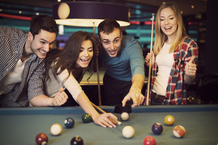 sports bar: Friends cheering while their friend aiming for billiards ball