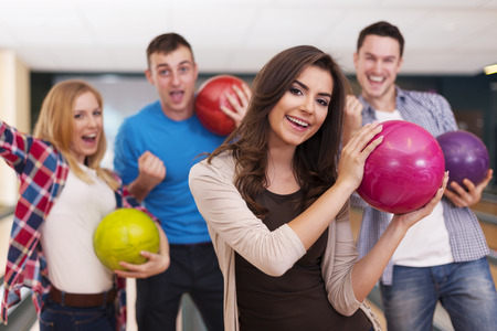bowling alley: Portrait of young woman with friends at bowling alley