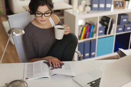 Aantrekkelijke vrouw lezing magazine thuis