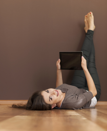 Happy woman lying on floor with digital tablet   photo