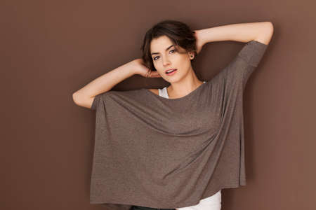 oversized: Gorgeous woman wearing oversized blouse posing on brown wall