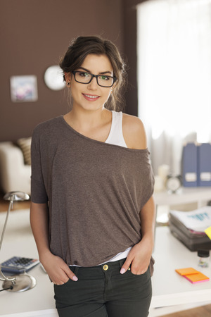 hand in pocket: Portrait of lovely woman in fashion glasses at home