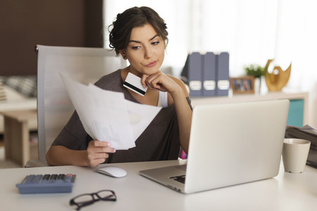 grimacing: Pensive woman paying bills at home  Stock Photo