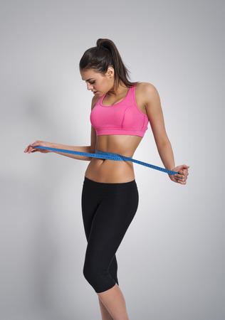 woman measuring waist: Focus woman measuring her waist after workout