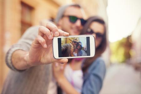 juveniles: Pareja joven de tomar selfie en la ciudad