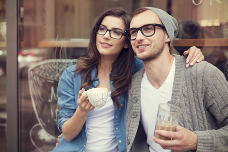 Young fashion couple drinking coffee outside of cafe