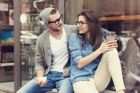 hombre tomando cafe: Los jóvenes se relajan con la taza de café fuera de la cafetería