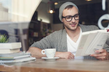 流行に敏感な人は、カフェで本を読んでの笑みを浮かべてください。