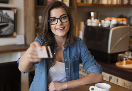 credit card: Smiling woman paying for coffee by credit card  Stock Photo