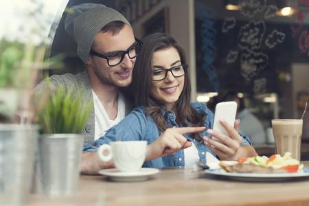 cafe internet: Pareja Abrazando el uso de tel�fono m�vil en caf� Foto de archivo