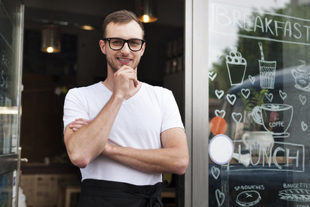business owner: Portrait of smiling male waiter outside the cafe
