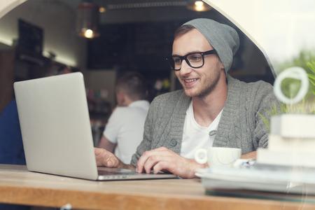 cafe internet: Inconformista hermoso que usa el ordenador portátil en el café