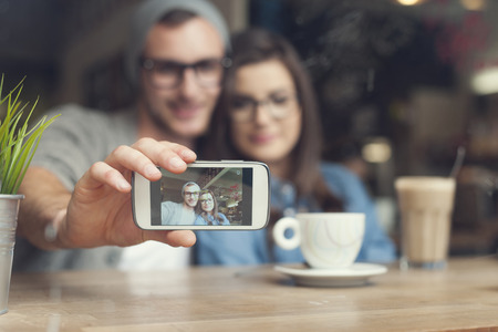 Hipster couple taking selfie at cafe