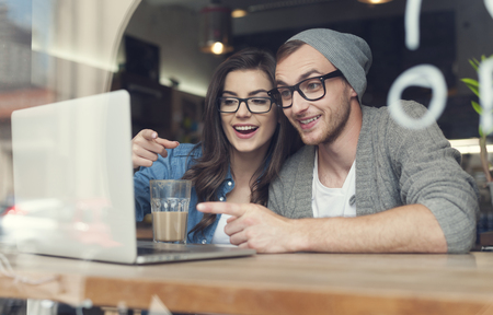 laughing couple: Couple have fun while looking on laptop at cafe