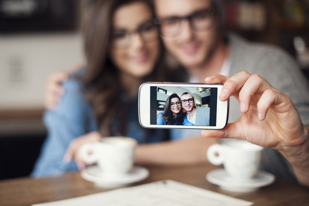Loving couple taking selfie at cafe Stock Photo