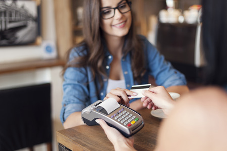pay desk: Smiling woman paying for coffee by credit card  Stock Photo