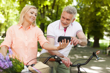 pareja madura feliz: Feliz pareja madura con la bicicleta que mira en el tel�fono m�vil