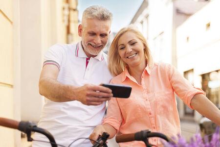 pareja madura feliz: Feliz pareja madura con tel�fono m�vil durante las vacaciones de ciclismo