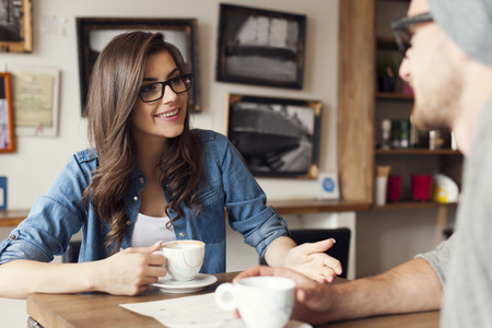 affectionate actions: Hipster couple talking at cafe  Stock Photo