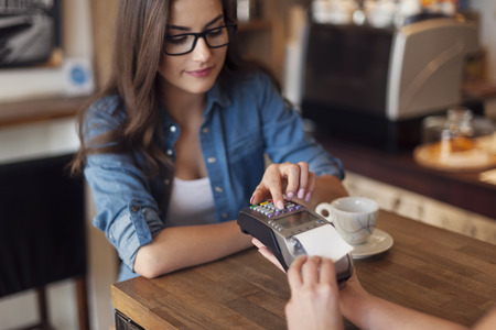 pay desk: Young woman paying for cafe by credit card reader Stock Photo