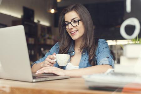 Mooie hipster vrouw met behulp van laptop in cafe