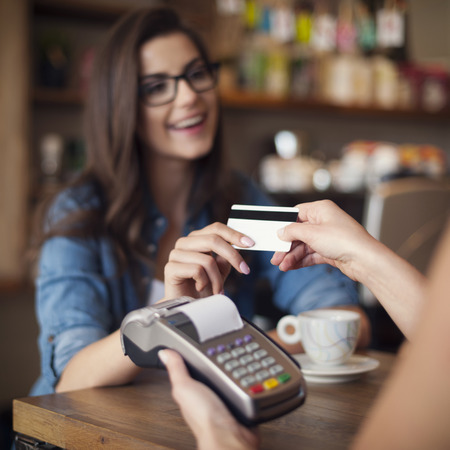 pay bill: Happy woman paying for cafe by credit card